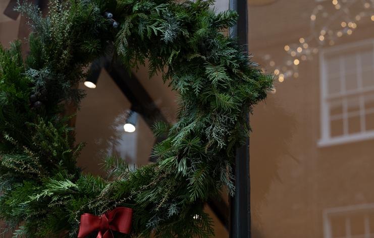 Christmas wreath with burnt orange ribbon hanging on shop window